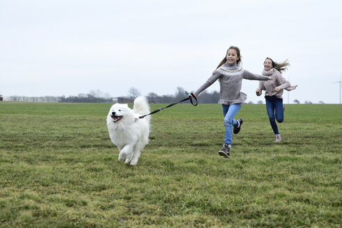 Two girls running on a meadow with  dog having fun - ECPF00261