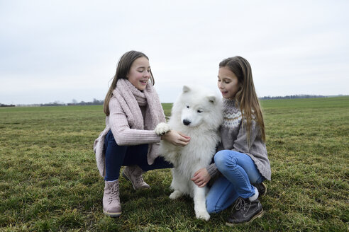 Two girls crouching on a meadow teaching dog - ECPF00264