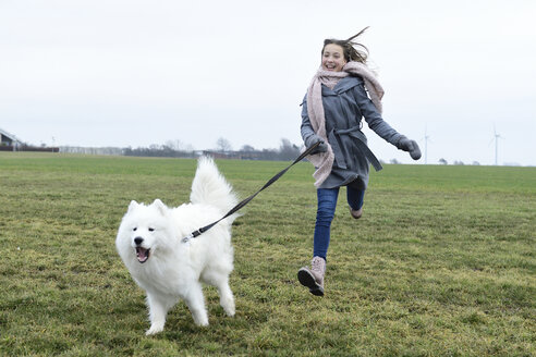 Laughing girl running on a meadow with her dog - ECPF00270