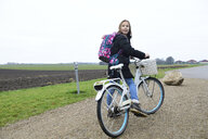 Girl with backpack and bicycle in rural landscape - ECPF00273