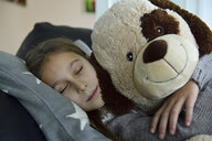 Portrait of girl relaxing on couch with her big soft toy - ECPF00279
