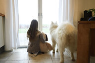 Back view of girl and her dog looking through French door - ECPF00282
