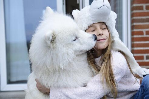 Girl hugging her dog on terrace - ECPF00285