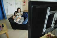 Two sisters watching television on couch - ECPF00288