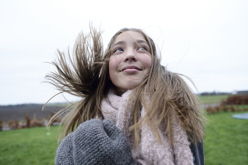 Portrait of smiling girl with blowing hair in winter looking up - ECPF00294
