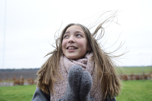 Portrait of smiling girl with blowing hair in winter - ECPF00297