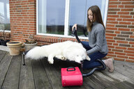 Girl blow-drying white dog on terrace - ECPF00300