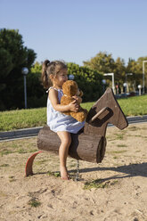 Little girl on rocking horse on a playground - MAUF02408