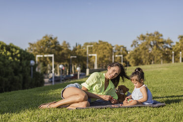 Happy mother playing with daughter on a blanket in park - MAUF02414