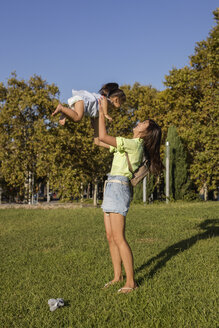 Happy mother playing with daughter in a park - MAUF02417