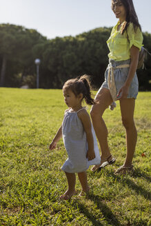 Little girl walking on lawn in a park with her mother - MAUF02420
