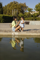 Happy mother with daughter at a pool in a park - MAUF02423