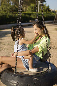 Happy mother with daughter on tire swing on a playground - MAUF02429