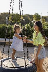 Happy mother with daughter on tire swing on a playground - MAUF02432