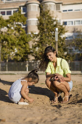 Smiling mother watching daughter playing in sand on a playground - MAUF02435