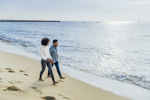 Spain, Barcelona, couple walking barefoot on the beach - BOYF01280