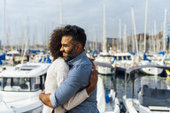 Spain, Barcelona, happy couple hugging at the marina - BOYF01292