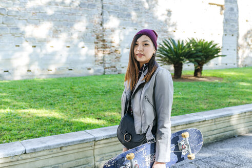 Portrait of young woman with skateboard - KIJF02202