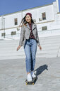 Portrait of smiling young woman standing on her skateboard - KIJF02205