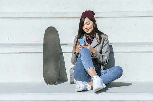 Smiling young woman sitting besides her skateboard looking at smartphone - KIJF02211