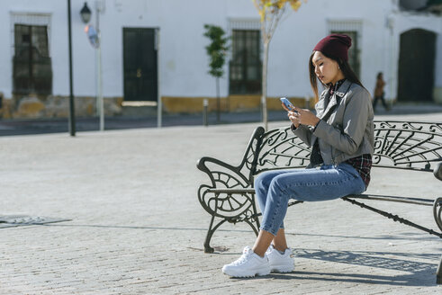 Young woman sitting on bench at square using smartphone - KIJF02217