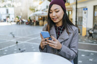 Portrait of young woman using smartphone at pavement cafe - KIJF02220