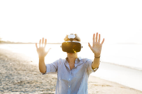 beautiful, blond, young woman is testing virtual 3D glasses, vr goggles on a wonderful beach in thailand, rayong - HMEF00182