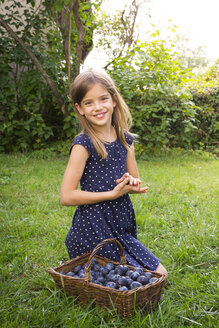 Portrait of smiling girl on a meadow with wickerbasket of plums - LVF07680