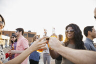 Friends toasting beer bottles at rooftop party - HEROF07684