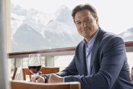 Portrait of confident businessman drinking wine on balcony - HEROF07744