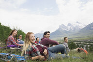 Friends relaxing in grass near mountains - HEROF07750