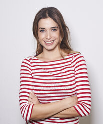 Portrait of smiling young woman wearing red-white striped shirt against light background - PNEF01165