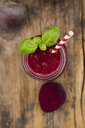 Glass of beet root smoothie garnished with basil leaves - LVF07688