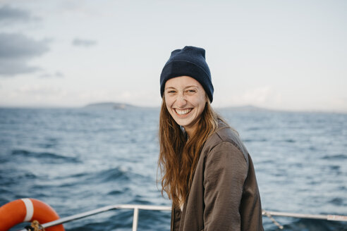 South Africa, young woman with woolly hat smiling during boat trip at sunset - LHPF00388