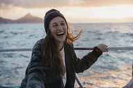 South Africa, young woman with woolly hat laughing during boat trip at sunset - LHPF00397
