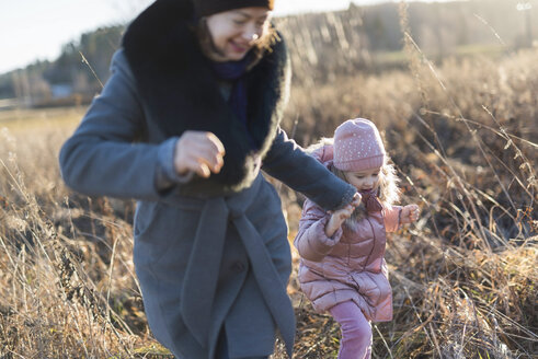 Little girl running hand in hand with her mother on autumnal meadow at Golden hour - PSIF00227