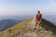 Italy, Monte Nerone, hiker on top of a mountain looking at panorama - WPEF01298