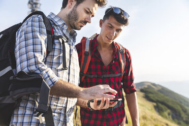 Italy, Monte Nerone, two men hiking and looking at smartphone in mountains - WPEF01301