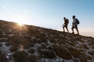 Italy, Monte Nerone, two men hiking in mountains at sunset - WPEF01307