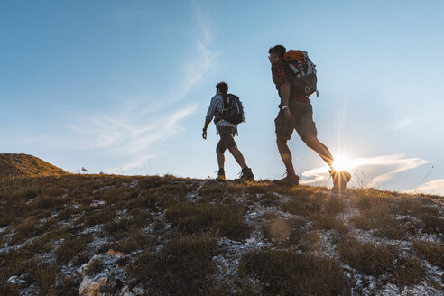 Italy, Monte Nerone, two men hiking in mountains at sunset - WPEF01310