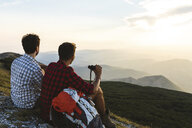 Italy, Monte Nerone, two hikers on top of a mountain enjoying the view at sunset - WPEF01313