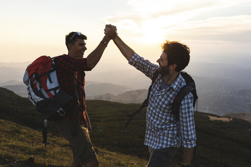 Italy, Monte Nerone, two happy and successful hikers in the mountains at sunset - WPEF01319
