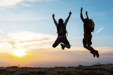 Italy, Monte Nerone, two happy and successful hikers jumping on top of a mountain at sunset - WPEF01322