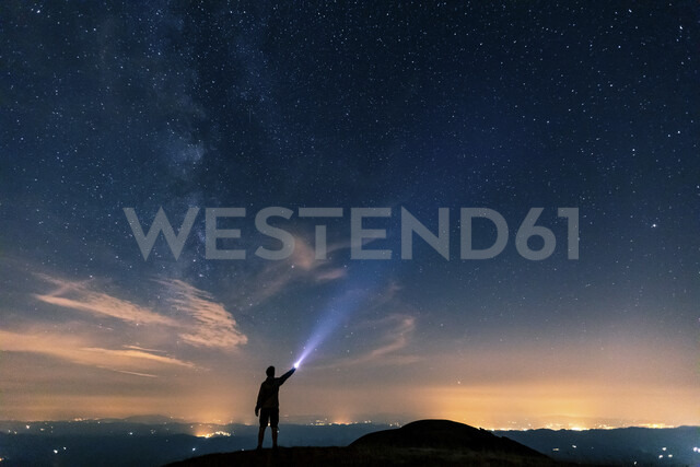 Italy, Monte Nerone, silhouette of a man with torch under night sky with stars and milky way - WPEF01328 - William Perugini/Westend61