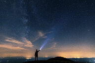 Italy, Monte Nerone, silhouette of a man with torch under night sky with stars and milky way - WPEF01328