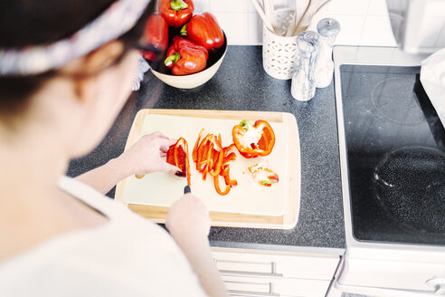 Cropped image of woman cutting bell pepper at kitchen counter - ASTF02756