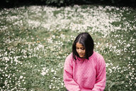 Happy young woman sitting on field in park - ASTF02783
