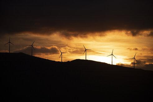 Spain, Andalusia, Tarifa, wind wheels on mountain at sunrise - KBF00463
