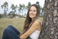 Portrait of smiling young woman leaning against tree trunk - PNEF01177