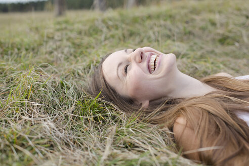 Laughing young woman lying on a meadow - PNEF01180